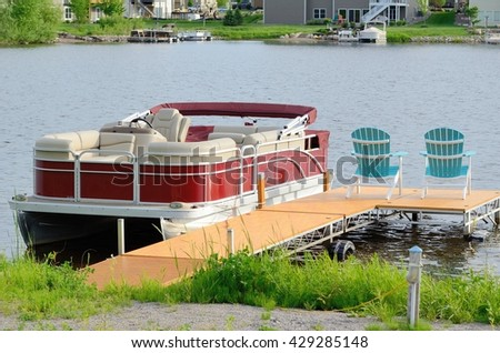 Red Pontoon Boat Tied to a Dock With Two Chairs - stock photo