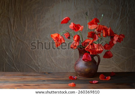 Red poppies in a ceramic vase on a wooden table - stock photo