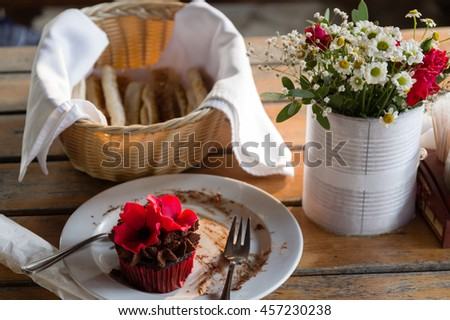 Red poppy flower cupcake on a wooden table with a white vase of roses and wild flowers