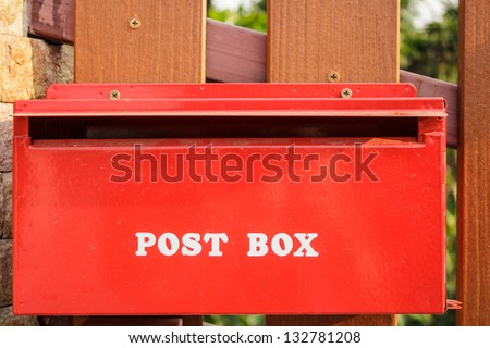 Red post box next to the fence - stock photo