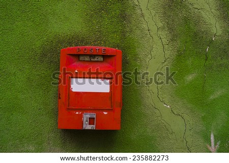 red post box on a green wall