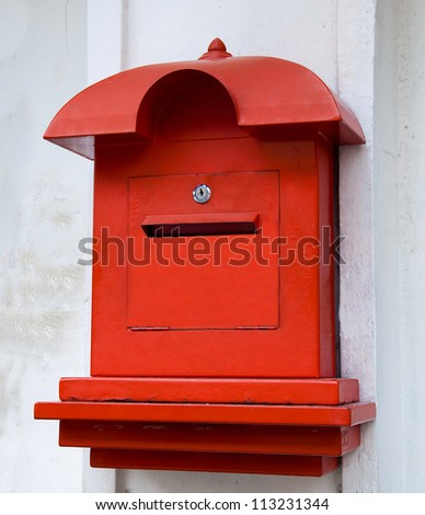 Red postbox  on white wall background - stock photo