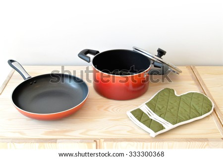 Red pot, pan and green glove on the cupboard at home.
