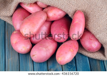 red potatoes in burlap sack on a blue wooden table - stock photo
