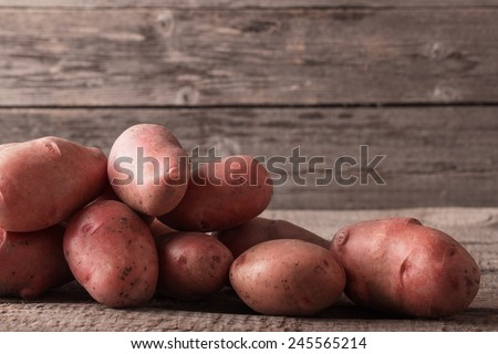 red potatoes on wooden background - stock photo