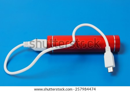 Red power bank on blue background - stock photo