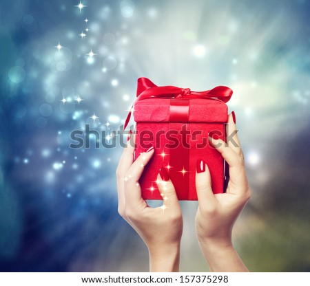Red present box on Christmas on shinning background being held up by in a woman's hands - stock photo