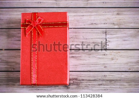 Red present box on wooden background - stock photo