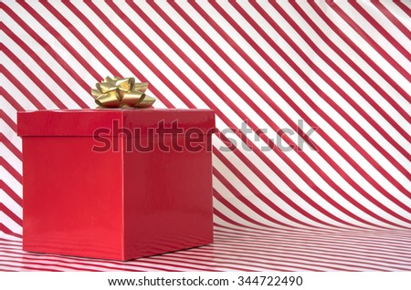 Red present on candy cane striped background with copy space.