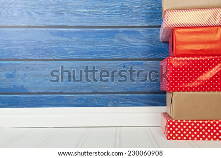 Red presents on white floor with blue wooden wall - stock photo