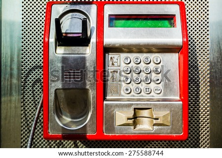 Red public telephone is attached on metallic background, phone and headset. - stock photo