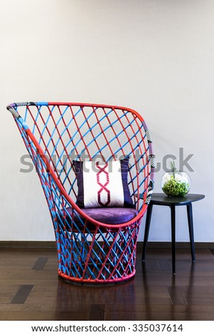 Red purple blue tone wicker chair in front of a plain wall - stock photo