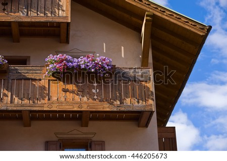 Red, purple, violet geranium flowers on wood balcony traditional alpine house. North Italy. Dolomites. Trentino Alto Adige. Summer in Alps.