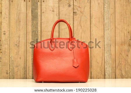 red purse on wood background, luxury women accessory - stock photo