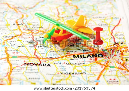 Red push pin pointing at Milano, Italy  map   and a taxi - stock photo