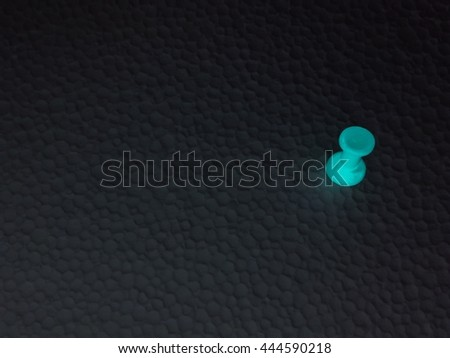 Red pushpin isolated on dark background - stock photo