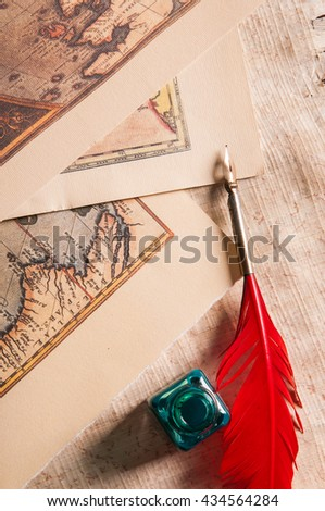 Red quill pen, a green inkwell and a rolled papyrus sheet with some old maps on a wooden table - stock photo