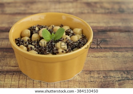Red quinoa salad with chickpeas garnish with mint leaf. Served on ramekin on wooden background  - stock photo