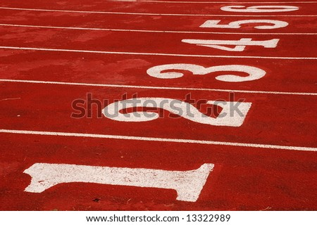Red race track with numbered lanes - stock photo