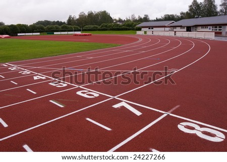 Red racetrack of stadium with soft covering near  houses and wood - stock photo