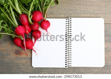 Red radishes nearby to the open notebook on a  brown wooden table