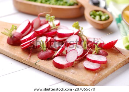 red radishes on wooden cutting board - stock photo
