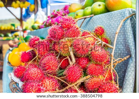 Red rambutan Nephelium lappaceum on the market. Fruit tropical tree of the family Sapindaceae , native to South - East Asia , cultivated in many countries in the region. On the market of Hawaii, Maui. - stock photo