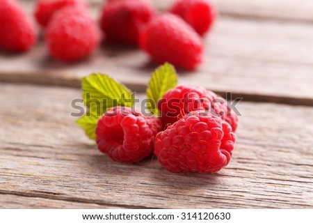 Red raspberries on grey wooden background - stock photo