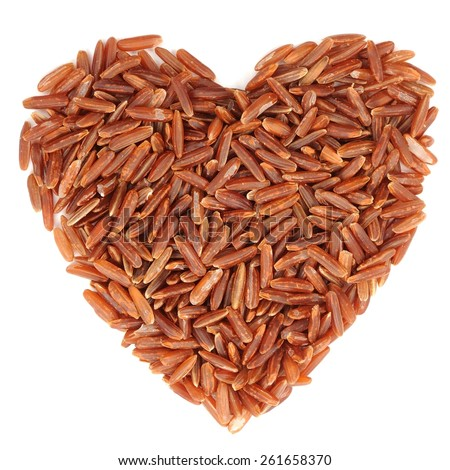Red raw rice in heart shape, isolated - stock photo