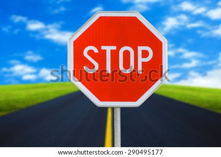Red realistic stop road sign on blurred road with sky