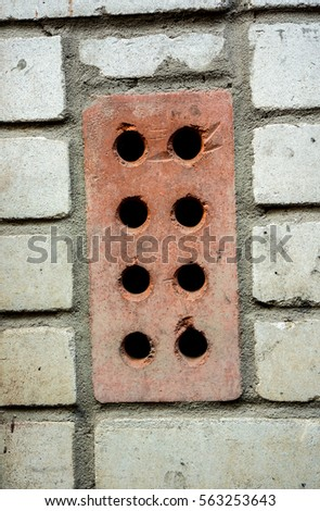 Red Rectangular Brick With Round Holes Arranged Vertically On A Large Wall Horizontal Smooth White