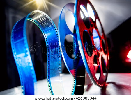 Red reel of blue film on a dark background - stock photo