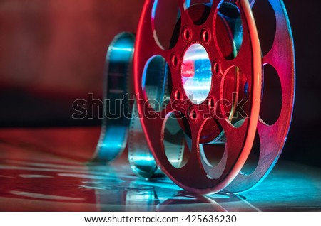 Red reel of film on a dark background - stock photo