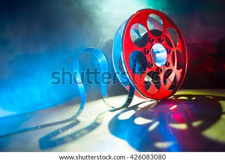 Red reel of film on a dark background with a smoke - stock photo