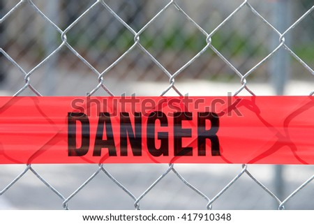 Red reflective danger barrier tape across a chain link fence to keep pedestrians out of construction zone, close up on word danger - stock photo