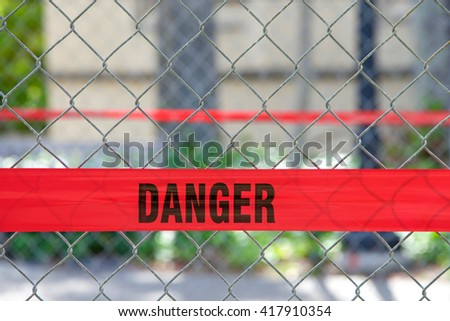Red reflective danger barrier tape across a chain link fence to keep pedestrians out of construction zone - stock photo
