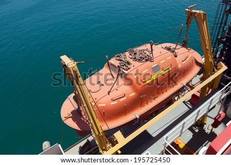Red rescue boat hanging on the passenger ship - stock photo