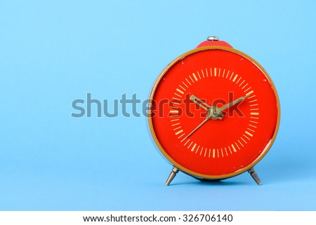 Red retro clock on blue background with copy space - stock photo