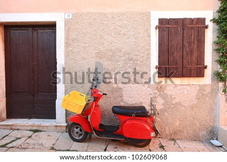 red retro motorcycle in old village - stock photo