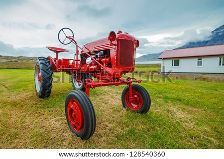 Red retro tractor on the Iceland field.