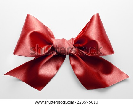 Red ribbon bow with real shadow on white background - stock photo