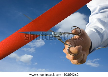 Red ribbon cutting with a pair of scissors for the inauguration of the new business activity - stock photo