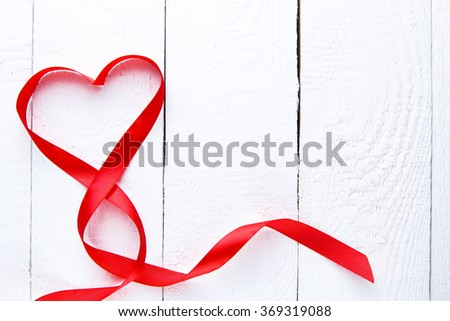 Red ribbon heart on white wooden background on valentine's day.
