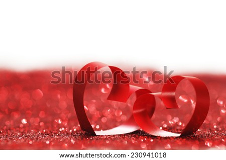 Red ribbon hearts on glitters isolated on white, Valentines day concept - stock photo