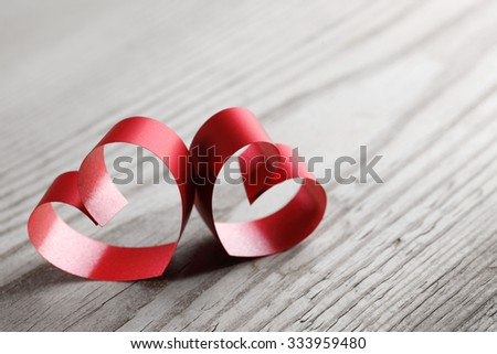 Red ribbon hearts on wooden background, Valentines day concept - stock photo