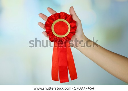 Red ribbon is symbol for success and  first prize, on light background - stock photo
