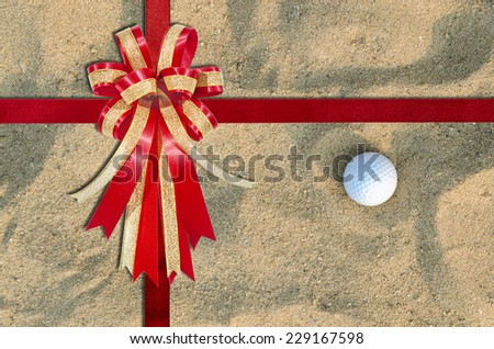 Red Ribbon on A golf ball on the sand for background ; top view - stock photo