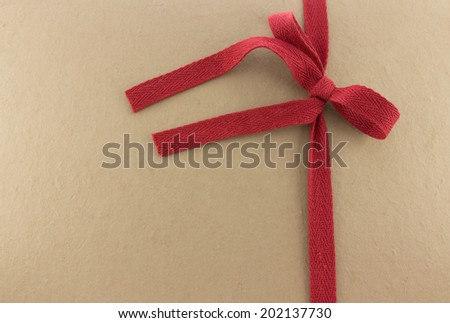 Red ribbon on brown mulberry paper background
