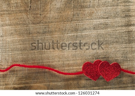 Red ribbon tape and hearts on wooden background. - stock photo