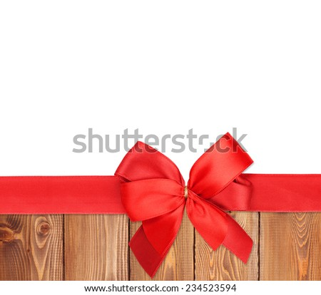 Red ribbon with bow over wood background with copy space - stock photo